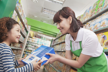 Female Sales Clerk Gives Little Girl Cereal Box