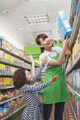 Female Sales Clerk Helping a Little Girl Reach a Cereal Box