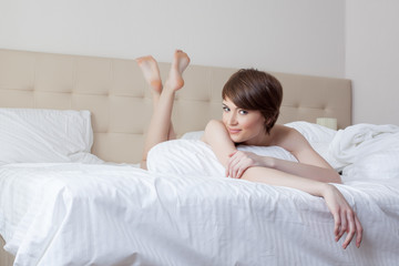 Cute young brunette with short hair posing in bed