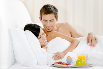 Lying man serves woman breakfast in bedroom