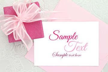 Gift box with ribbon and white invitation card
