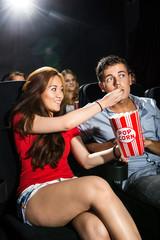 Woman Feeding Popcorn To Boyfriend In Theatre