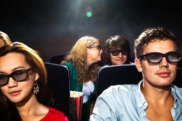 Woman Whispering In Boyfriend's Ear In Cinema Theatre