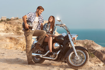 Wall Mural - Stylish couple on a motorcycle. He put his foot on the exhaust p