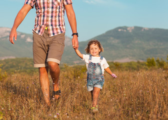 Wall Mural - Father and daughter walking on the field