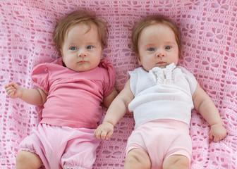 Sweet little  twins lying on a pink blanket.