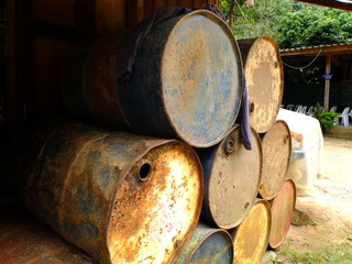 pile of rusty old empty oil barrel