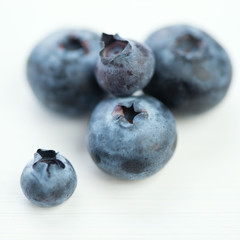 Macro shot of ripe blueberries on white wooden background