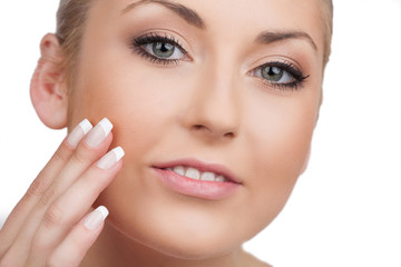 Skin care. Close-up of cheerful woman looking at camera and touc