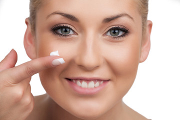 Skin care. Close-up of cheerful woman spreading cream on face