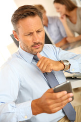 Attractive businessman with blue shirt using smartphone