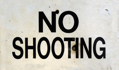 Grungy No Shooting Sign With Bullet Holes
