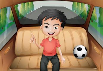 A boy inside the car with a soccer ball