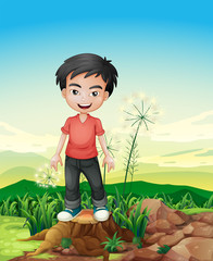 A smiling boy standing above a stump