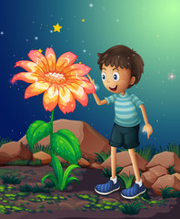 A young boy beside the giant flower