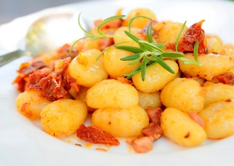 Gnocchi with tomatoes, bacon and onion on the white plate.