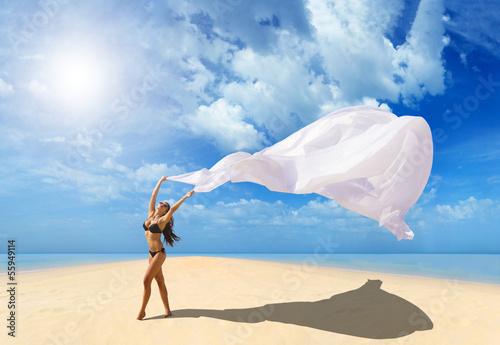 Девушка на пляже в развивающимся на ветру плье бесплатно