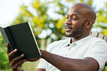 Handsome Black Man Reading Book at Park