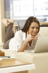 Happy woman browsing internet at home