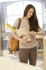 Young woman checking time as getting home