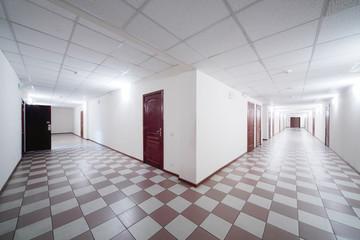 Two long hallways with brown wooden doors and floor