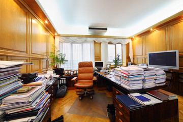 Leather armchair and tables with many folders with papers