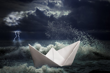 paper ship in storm concept