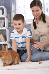 Mum and son with pet rabbit at home