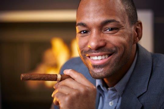 Happy ethnic man smoking cigar