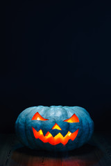 Halloween pumpkin on black background with copy space above it
