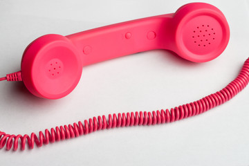 Pink phone and cord on white surface