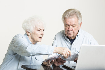 Senior couple is looking at the bills concerned