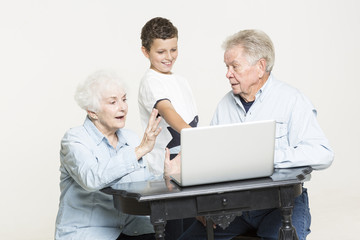 Young boy helps his grandparents with computer problem