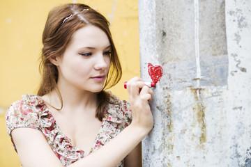 Woman in dress draw heart on wall