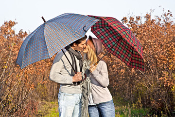Couple kissing under umbrellas in the autumn park.