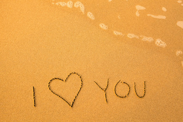 I Love You - text written by hand in sand on a beach