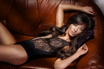Beautiful brunette woman lying on sofa.