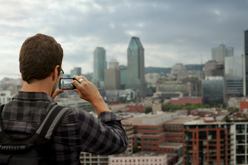 Man Taking a Picture of Downtown Montreal