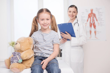 Child on medical exam. Cheerful little girl looking a camera and