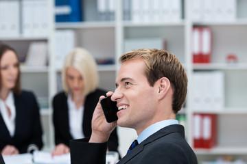 geschäftsmann telefoniert mit seinem handy im büro