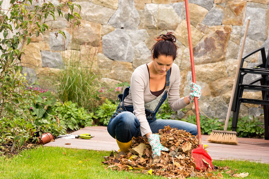 Young woman raking leaves autumn pile veranda