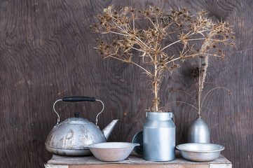 Kitchen utensils on the wooden background with dry flowers