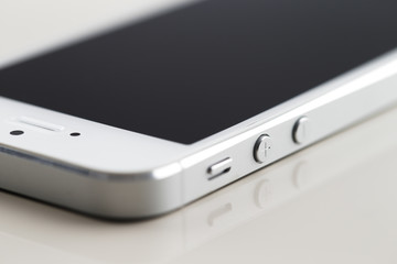 A new white smartphone on a white reflective background