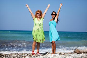 Zwei Frauen am Strand halten ihre Hände hoch