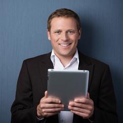 lächelnder mann hält tablet-pc in der hand