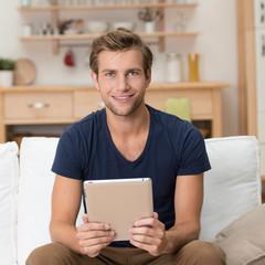 junger mann liest zuhause am tablet-pc