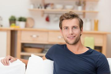 junger mann sitzt entspannt auf dem sofa