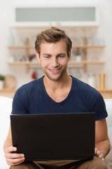 mann sitzt mit laptop auf dem sofa