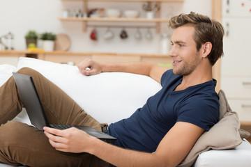 mann liegt entspannt mit seinem laptop auf dem sofa