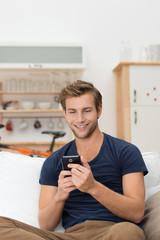 junger mann zu hause schaut auf sein smartphone